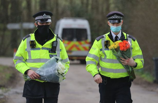 Police carry flowers at Great Chart Golf and Leisure near Ashford in Kent following the discovery of human remains in the hunt for missing Sarah Everard