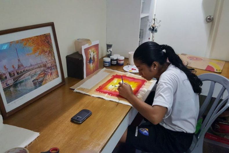 Young Filipino girl sitting at a desk painting