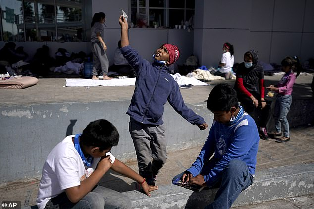 A migrant boy (center) in Reynosa, Mexico launches a paper airplane while playing with other migrant children at a plaza near the McAllen-Hidalgo International Bridge point of entry into the United States after being caught trying to cross into the US and deported
