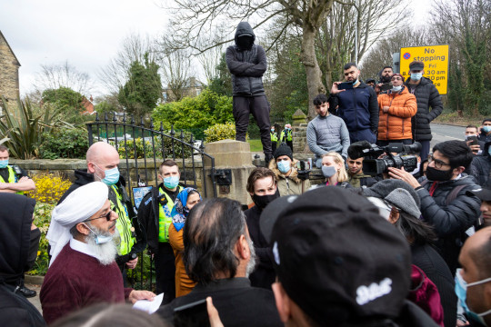 A local community leader speaks to the crowd of parents. Angry parents are protesting outside a Batley Grammar School, West Yorks, after a teacher allegedly showed derogatory caricatures of the Prophet Muhammad, pictured in West Yorks, March 25 2021.