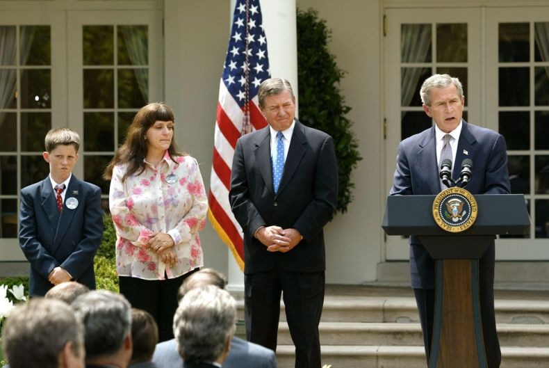 President George W. Bush speaks before signing Amber Alert legislation into law during a Rose Garden ceremony at the White House on Wednesday, April 30, 2003. The law creates a nationwide voluntary rapid-response network to help find kidnapped children. Bush is joined by Attorney General John Ashcroft, center, and Donna Norris, second from left, the mother of the bill's namesake, 9-year-old Amber Hagerman who was abducted in 1996 in Arlington, Texas, and later found murdered. Her son Rick Hagerman stands at far left.