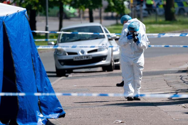 A forensics officer takes photographs at the scene on College Road, Kingstanding, north of Birmingham, where a 14-year-old boy died after being stabbed on Monday evening. Police have launched a murder investigation and are hunting up to seven people in connection with the attack. Picture date: Tuesday June 1, 2021.