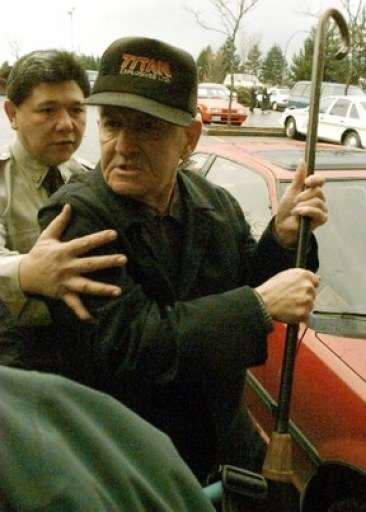 Arthur Plint threatens a photographer with his cane after arriving at the Port Alberni Courthouse.