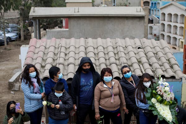 Relatives of a man who died of Covid-19 at his burial in Lima, Peru, on Tuesday.