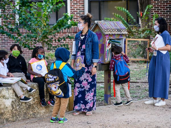 Students and teachers wearing their school-required masks wait for parents to arrive outside Lamar Elementary School in San Antonio, Texas.