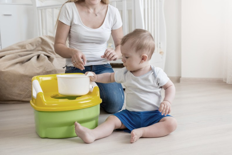 a toddler sits by a training potty with his mom