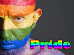 Gay flag painted on the face of a man. Man is looking at camera and has a serious expression. The word Pride is written at one side.