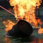 Barrel of oil on fire floating in water