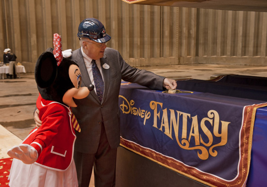 With assistance from Minnie Mouse, Karl Holz, President of Disney Cruise Line, places the coin in the keel for the Disney Fantasy.