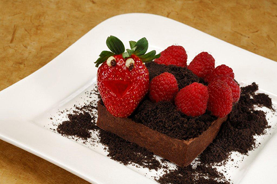 """The Worms & Dirt Tart Topped with a Smiling Strawberry, Fresh Raspberries, and Chocolate Cookie """"Dirt"""" Crumbs"""