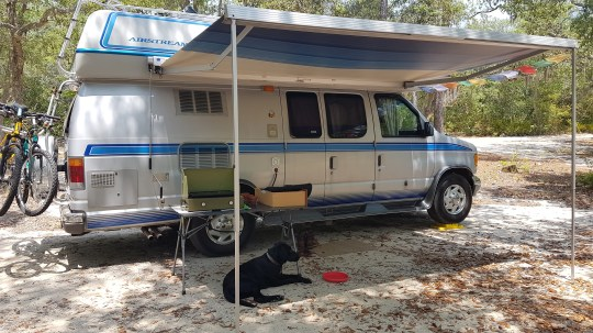 Our van with awning out (and a friendly dog)