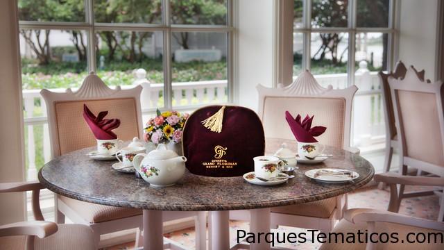 Toma el té en una delicada taza adornada con rosas y mantén la infusión caliente con cubreteteras. Mesa con un juego de té de porcelana adornado con rosas y cubretetera de Disney's Grand Floridian Resort & Spa