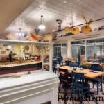 Bienvenido a la comunidad ficticia de Key West de Conch Flats, donde la residente de toda la vida Olivia maneja este café acogedor, en el que se sirven platos de cocina americana con un toque caribeño en un ambiente playero relajado. Te sentirás como en casa en el instante en que pases por la puerta. Modelo de barco en una vitrina cerca de las mesas y sillas de Olivia's Café