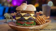 Dale un bocado a una Gigantosaurus Burger o ataca una Layers of the Earth Lasagna. Nuestra colosal selección de aperitivos, platos principales y postres te convencerá que la excelencia no se extinguió. Dos hamburguesas de carne en un panecillo con anillo de cebolla, tocineta, lechuga, tomate, pepinillos, queso y papas rejilla