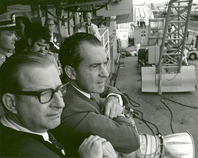 President Richard M. Nixon and Dr. Thomas O. Paine, NASA Administrator, watch Apollo 11 astronauts Neil A. Armstrong, Michael Collins and Buzz Aldrin Jr., walk from the recovery helicopter to the Mobile Quarantine Facility aboard the U.S.S. Hornet. The President later congratulated the astronauts by microphone, speaking through a window of the quarantine trailer. During the eight-day space mission, Armstrong and Aldrin explored the Moon's surface and brought back rock samples for scientists to study. Collins piloted the command module in the lunar orbit during their 22-hour stay on the moon. The extravehicular activity lasted more than two hours.