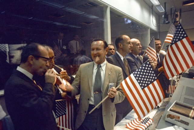 (July 24, 1969) NASA and Manned Spacecraft Center (MSC) officials join the flight controllers in celebrating the conclusion of the Apollo 11 mission. From left foreground Dr. Maxime A. Faget, MSC Director of Engineering and Development; George S. Trimble, MSC Deputy Director; Dr. Christopher C. Kraft Jr., MSC Director fo Flight Operations; Julian Scheer (in back), Assistant Adminstrator, Office of Public Affairs, NASA HQ.; George M. Low, Manager, Apollo Spacecraft Program, MSC; Dr. Robert R. Gilruth, MSC Director; and Charles W. Mathews, Deputy Associate Administrator, Office of Manned Space Flight, NASA HQ.