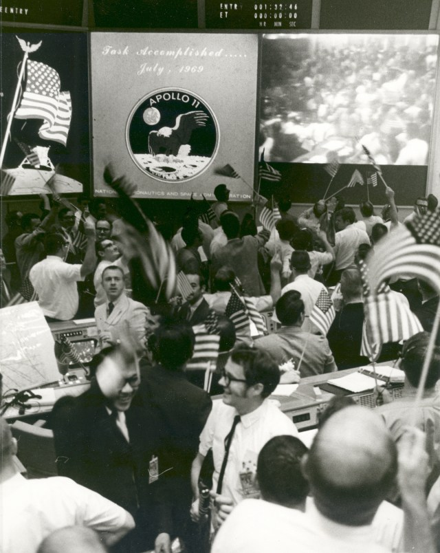 Overall view of the Mission Operations Control Room in the Mission Control Center, Building 30, Manned Spacecraft Center, showing the flight controllers celebrating the successful conclusion of the Apollo 11 lunar landing mission.
