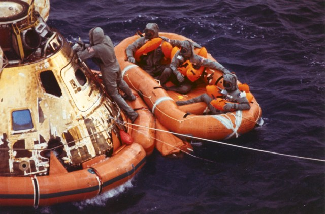 (July 24, 1969) Pararescueman Lt. Clancy Hatleberg closes the Apollo 11 spacecraft hatch as astronauts Neil Armstrong, Michael Collins, and Buzz Aldrin, Jr., await helicopter pickup from their life raft. They splashed down at 12:50 pm EDT July 24, 1969, 900 miles southwest of Hawaii after a successful lunar landing mission.