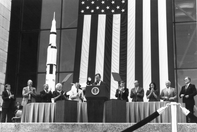 (July 20, 1989) President George Bush speaks at the National Air and Space Museum's 20th anniversary celebration of the Apollo 11 Moon landing. Here, on July 20, 1989, Bush announced his new Space Exploration Initiative, which was to complete the space station, return man to the moon, and bring man to Mars for the first time. The plan fell apart when NASA offered an estimated budget of 500 billion over the next 20 to 30 years to achieve the President's goal. Congress balked, and NASA returned to its earlier program of primarily robotic space exploration. From left to right are NASA Administrator Admr. Richard Truly, First Lady Mrs. Barbara Bush, Neil Armstrong, President George Bush, Vice President Dan Quayle, Michael Collins, Mrs. Marilyn Quayle, and Buzz Aldrin.