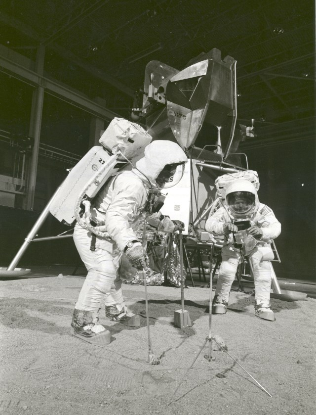 (April 21, 1969) Two members of the Apollo 11 lunar landing mission participate in a simulation of deploying and using lunar tools on the surface of the Moon during a training exercise on April 22, 1969. Astronaut Buzz (Aldrin Jr. on left), lunar module pilot, uses a scoop and tongs to pick up a soil sample. Astronaut Neil A. Armstrong, Apollo 11 commander, holds a bag to receive the sample. In the background is a Lunar Module mockup.