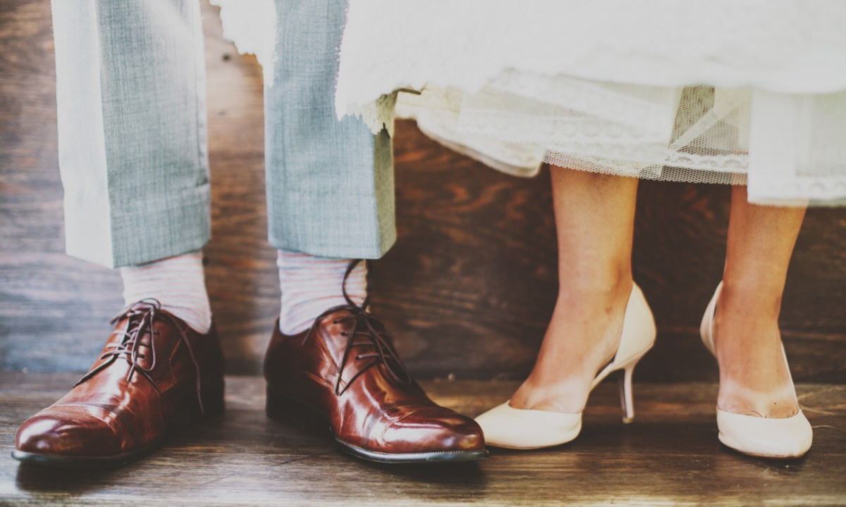 men's feet in dress shoes next to woman's feet in heels