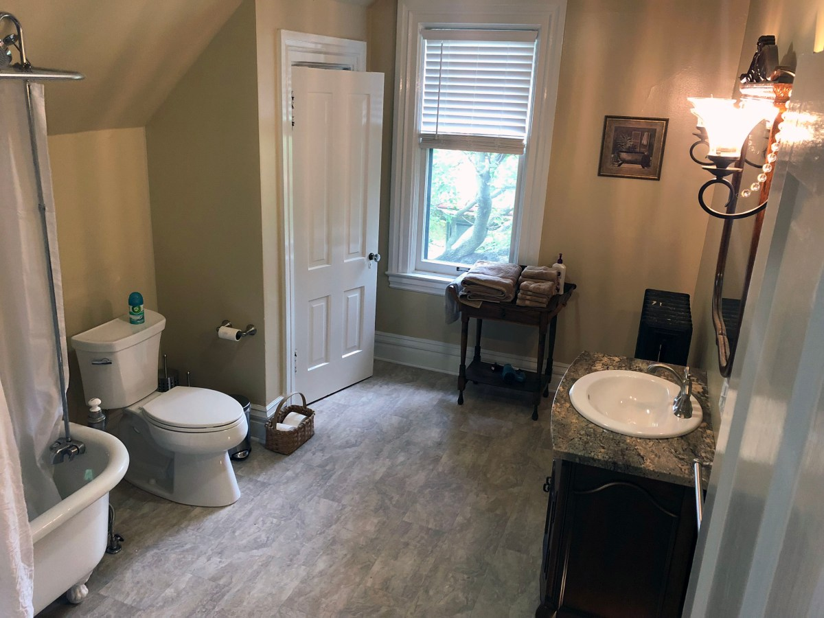 tub, toilet, lavatory, and towels on stand in front of window
