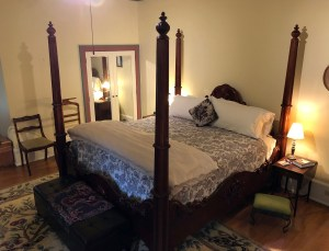 four-poster king bed in front of mirrored closet door