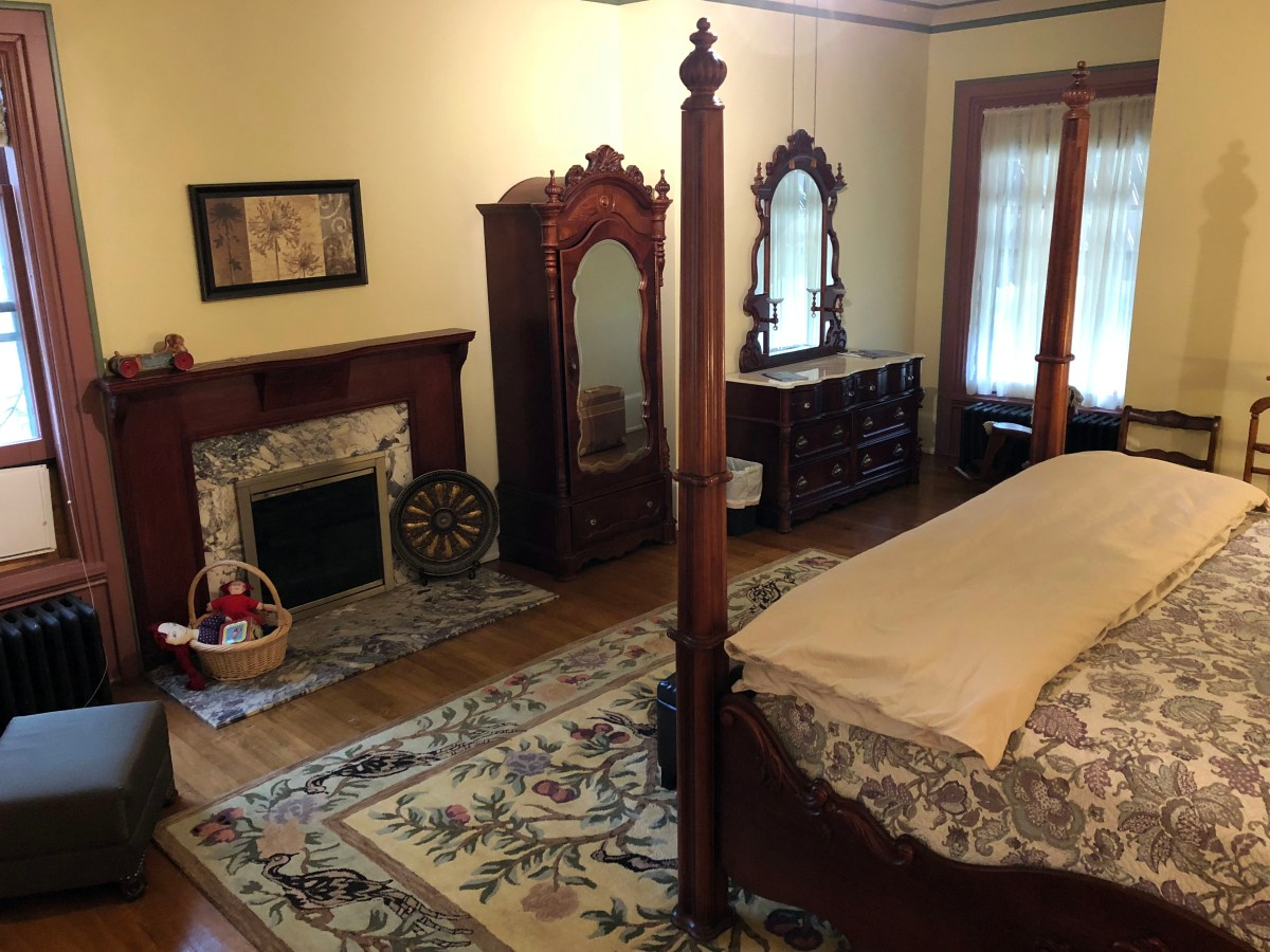 corner of bed in front of fireplace, mirrored cabinet, and dresser