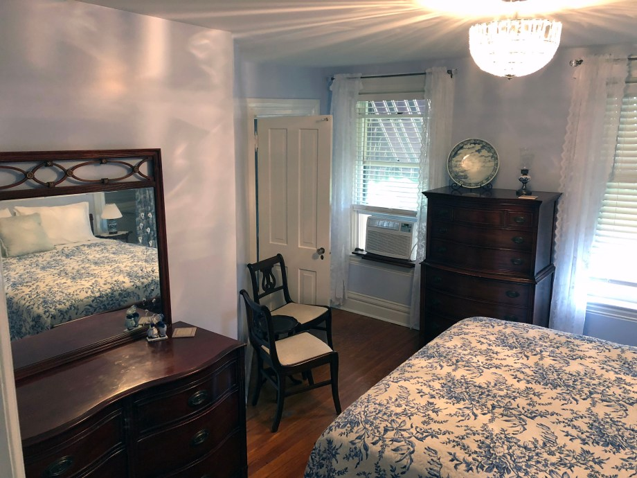 queen bed, dresser with mirror, chairs, and chest of drawers in room 5