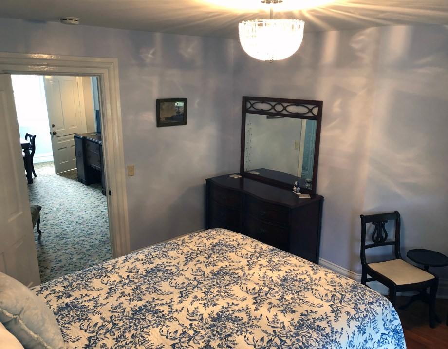 queen bed and dresser with mirror in room 5