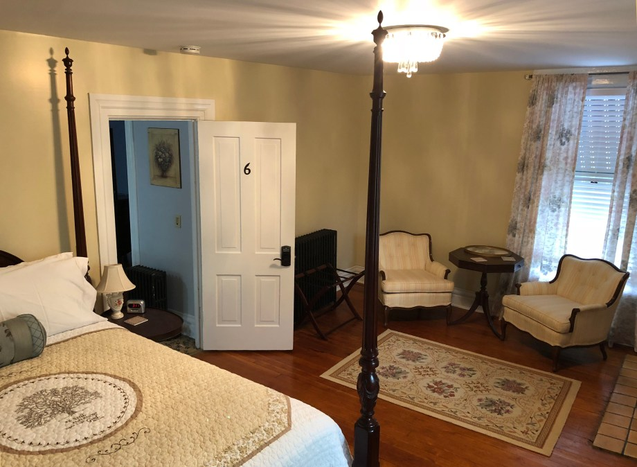 a bed, chairs and door of Room #6