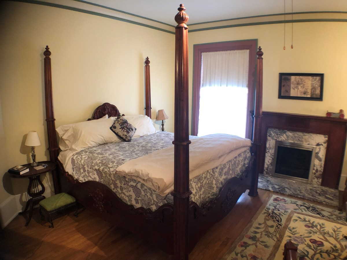 Four-poster King bed near a fireplace