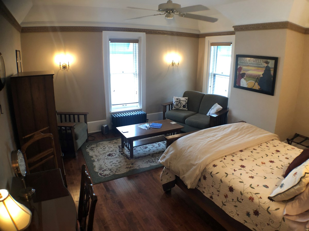 View of room 4 with bed, coffee table, chairs