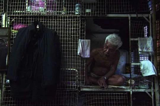 """Un homme en cage dans la citadelle de Kowloon (Hong-Kong) - image tirée du film documentaire """"le Syndrome du Titanic"""""""