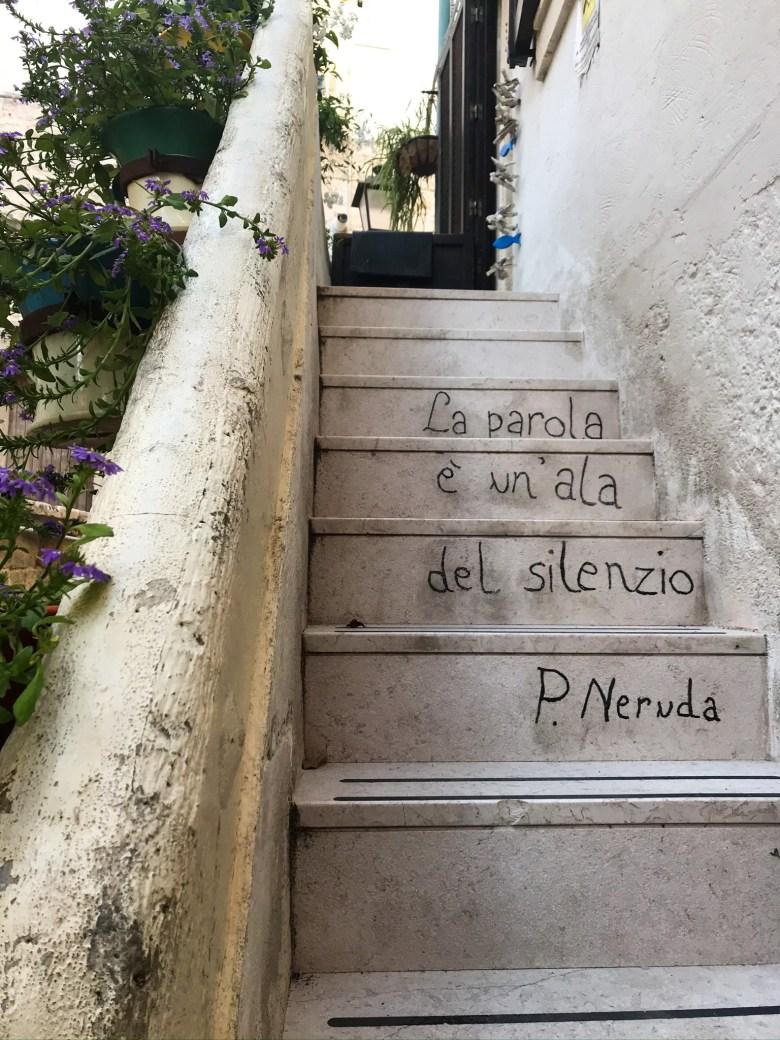 Frase di Pablo Neruda sulle scale di una casa a Polignano
