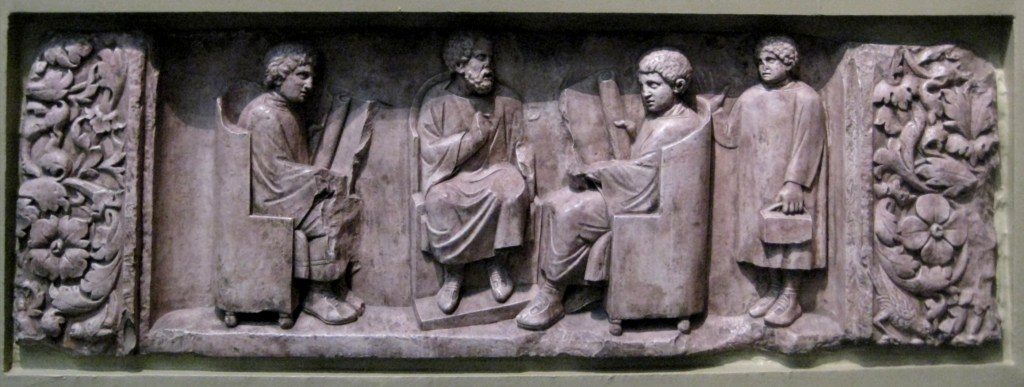 Relief found in Neumagen near Trier, a teacher with three discipuli. Around 180–185 CE. Photo of casting in Pushkin museum, Moscow. Wikimedia Commons