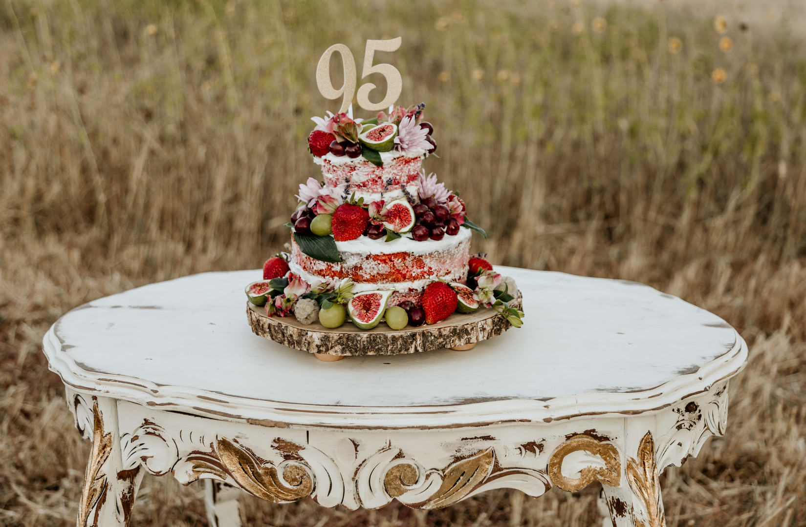 Looking for a unique birthday cake for your next party? Check out this awesome 95th birthday cake covered in flowers and fresh fruit! Featuring a 95th birthday cake topper too, this birthday photo shoot will give you ideas for decoration too! #birthdaycake #birthdays #birthdayparties #birthdaycaketopper #photoshoots
