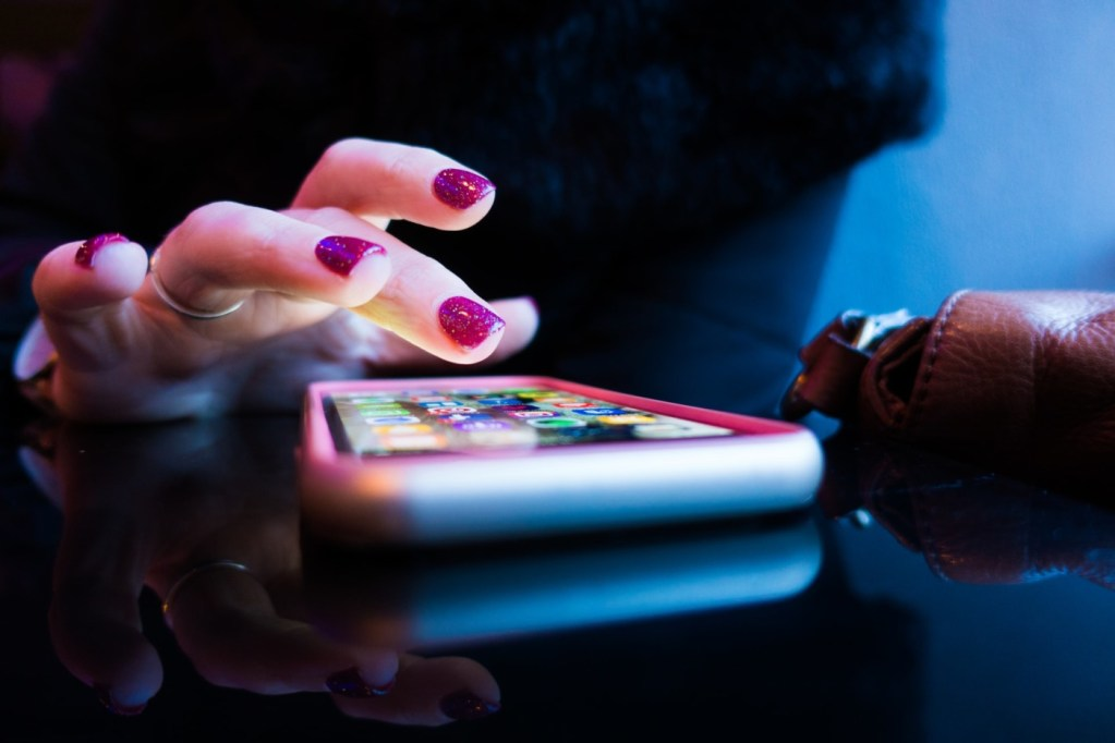 A woman taps her smartphone screen