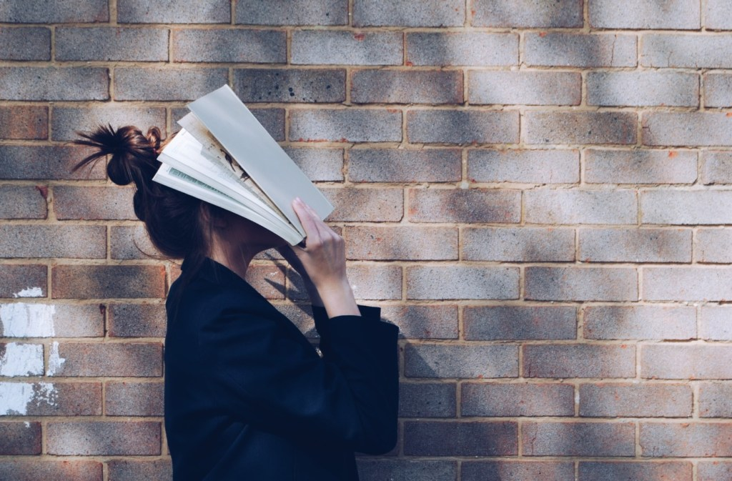 student with an open book covering their face
