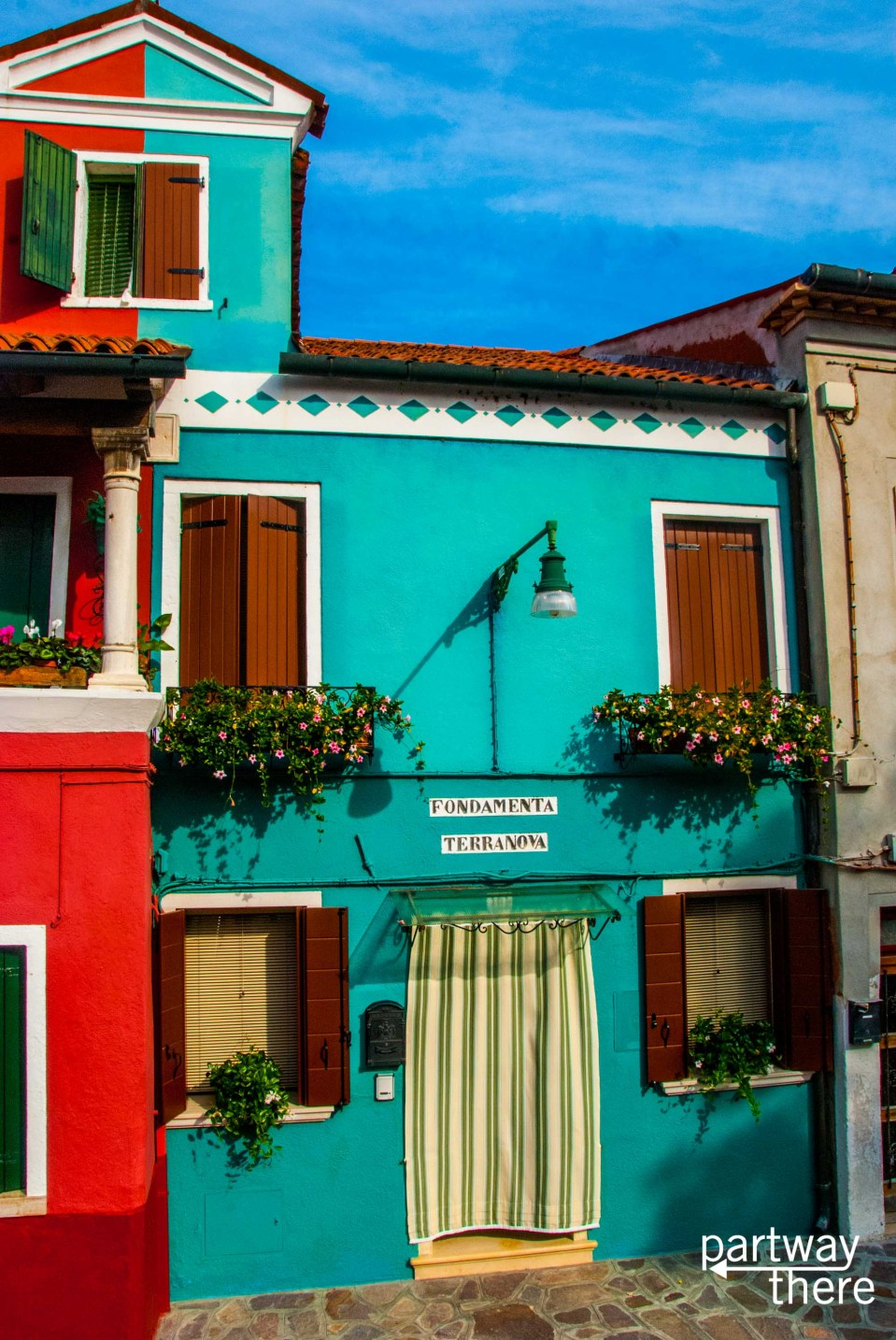 Teal house with flowerboxes in Murano, Venice, Italy