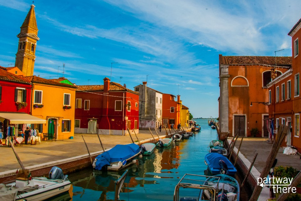 Boats, houses, and belltower along the canal in Burano, Venice
