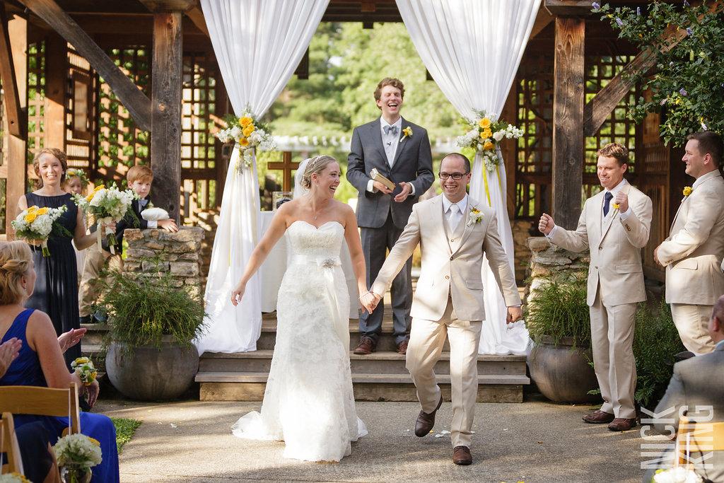 wedding couple walking aisle hand in hand