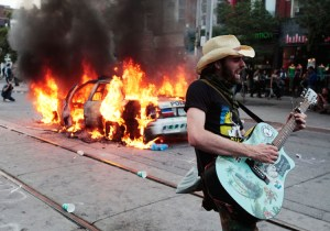 A man plays guitar in front of a burning police car during a protest against the G20 summit in downtown Toronto