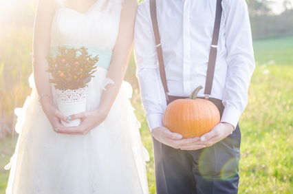 Bride and groom holding flowers and pumkin