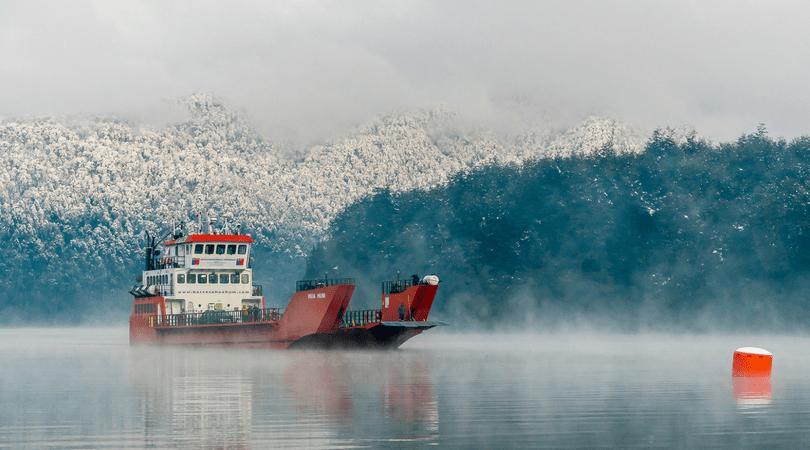 La barcaza Hua Hum cruzando el lago Pirehuico rumbo al paso fronterizo con Argentina, con los árboles nevados