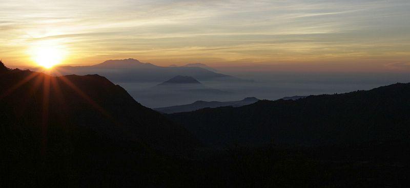 Atvirukinė Indonezija. Tolumoje - rūke skęstantis Semeru ugnikalnis, iš kurio tikimasi bet ko ir bet kada.