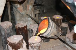 Liquid bronze at 1200 °C is poured into the dried and empty casting mould