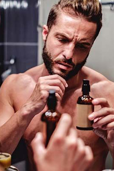 homme utilisant de l'huile de rasage pour préparer sa peau