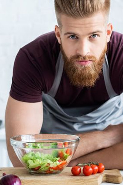 homme mangeant des légumes pour favoriser la pousse de la barbe