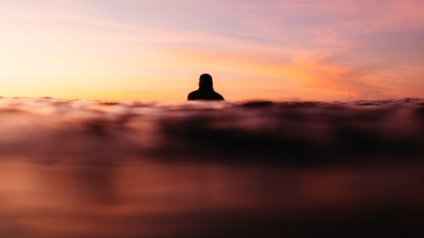 surfer half-submerged in the ocean at sunset